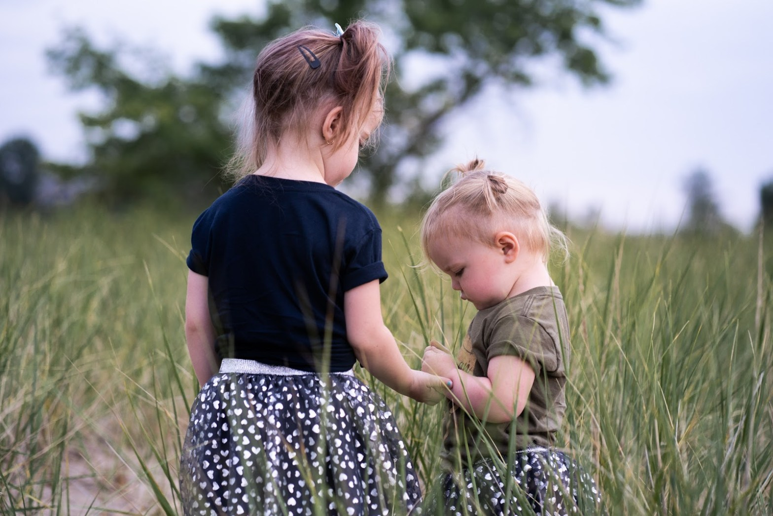 Young girls playing in the grass.